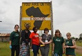Swahili volunteers pose for a picture at the ecuator sign