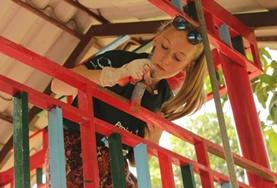 A volunteer paints and repairs a structure on a Care and Community placement in Cambodia