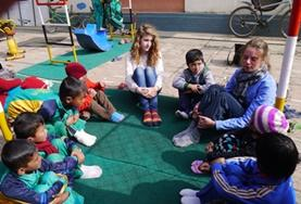 A Care and Community volunteer sits with children at a placement in Nepal