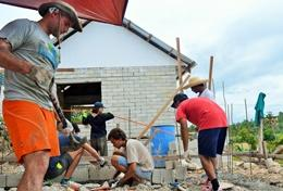 Volunteers work on the construction of a foundation for a new classroom being built in the Philippines.