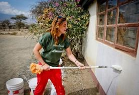 A Building volunteer paints the wall of a completed school building at her placement in Tanzania.
