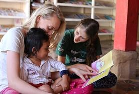 Two Care volunteers read to a child at a local daycare centre in Cambodia.