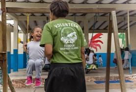A childcare volunteer pushes a young girl on a swing in a playground in Ecuador.