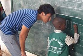 A childcare volunteer teaches a local child in Senegal how to write using a blackboard.