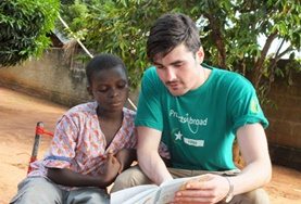 A childcare volunteer reads to a boy in Togo, working on his English literacy skills.