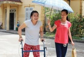 A Care volunteer works with a disabled child in Vietnam, helping her to walk and exercise.