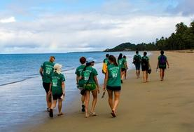 Volunteers walk along the beach in Fiji