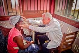 A volunteer inspects a patient while on a Doctor Project placement in Ghana
