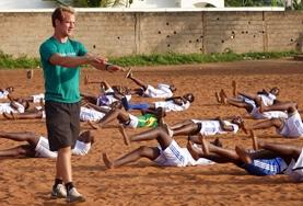 A Physical Education Teaching volunteer runs a fitness session with students on a placement in Ethiopia