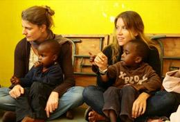 Care volunteers sit with children at their placement in Kenya