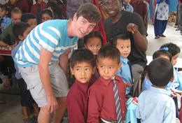 A Care and Community volunteer poses with children at a placement in Nepal