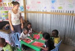 A High School Special volunteer holds an art class to teach children at a daycare centre in South Africa how paint.