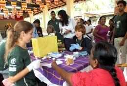 A Medicine High School Special volunteer measures a child's blood pressure at a healthcare outreach in Sri Lanka, Asia.