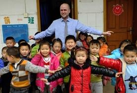 A Teaching volunteer plays an interactive educational game with local school children in China.