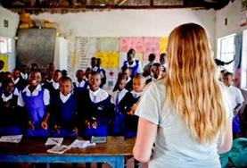 A teaching volunteer stands in front of a classroom at a placement in Kenya