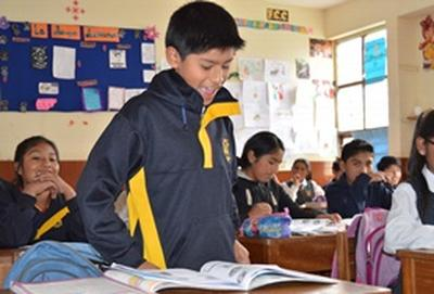 A students speaks in a classroom with a Teaching volunteer in Peru