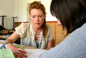 Teaching volunteers in Romania work together on a lesson plan to teach English to children at a local school.