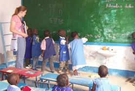 School children in Senegal work together to solve a problem on the blackboard at out volunteer Teaching placement in Senegal.