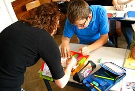 A Frecnh teaching volunteers works with a student at a placement in Romania